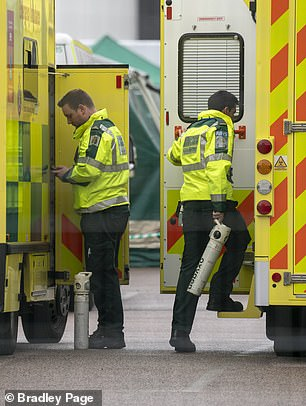 Paramedics are pictured carrying oxygen tanks into ambulances outside the NHS Nightingale Hospital in London today