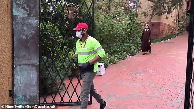 The delivery man was wearing protective gear and almost got caught by the large doors that protect the monastery