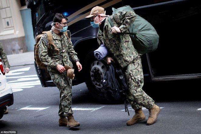 U.S. Navy personnel unload their gear from a bus as they arrive in Manhattan during the outbreak of the coronavirus disease