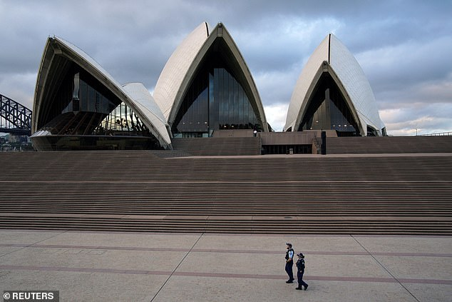 Health experts say that the key to stabilizing infections in Australia has been widespread testing, tracing carriers, self-isolation of those at risk and strict rules of social distancing. Two police officers are photographed on the forecourt of the Sydney Opera House on April 6