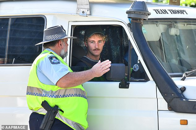 A policeman is shown talking to a driver at a checkpoint on the border between New South Wales and Queensland. Australians asked to stay at home during pandemic