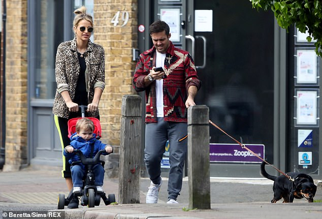 Glued to his phone: Spencer wore an Aztec-print jacket over a white T-shirt and grey joggers for the outing, keeping a handle on Winston's leash