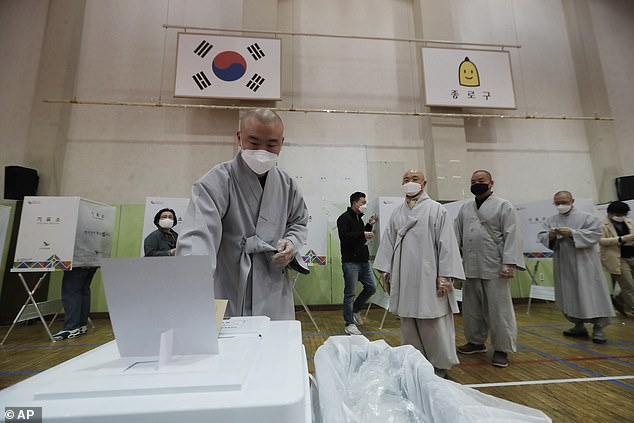 The country is still taking its epidemic seriously before next week's general election, and a Buddhist monk wearing a face mask is pictured voting early