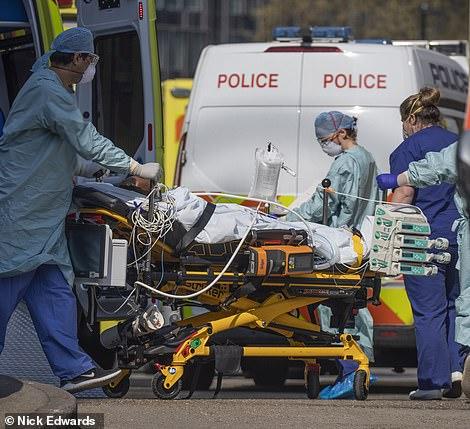 Los paramédicos que usan equipo de protección llevan a un paciente al Hospital St Thomas 'en el centro de Londres, donde el Primer Ministro Boris Johnson está siendo atendido