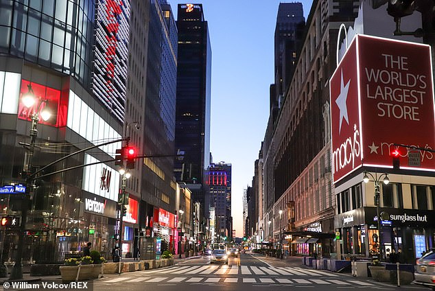 Three new reports predict that American life will not return to normal for more than a year, until a vaccine is available. Pictured: Times Square near empty Thursday