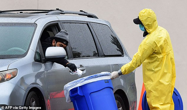 A driver of a vehicle drops his COVID-19 test in a bin on a mobile coronavirus test site in Los Angeles on Friday. Harvard says up to 100 million tests a day may be needed
