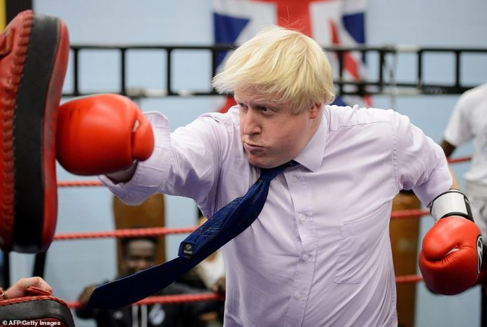 Boris Johnson boxing with a coach during his visit to the Fight for Peace Academy in North Woolwich, London, 2014 while he was mayor of London