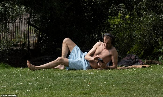 Another bather relaxes in Battersea Park on a warm Sunday Easter morning in London
