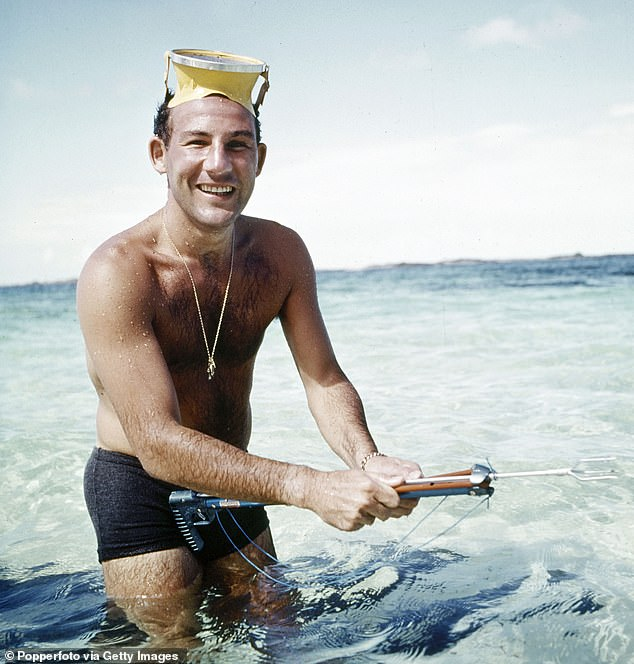 British racing driver Stirling Moss photographed in the Caribbean as he tries his hand with a