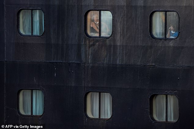 While most media have focused on the plight of passengers aboard cruise ships, thousands of crews have remained stranded. The crew is seen looking out the window of Holland America's Rotterdam on April 2 while they remained on board after the passenger evacuation