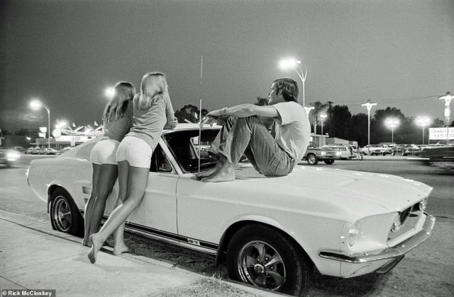 'Every town in America had a strip where kids would take their cars and go hang out whether it was only a block long - big towns, little towns, cities. It was really a thing for everybody to be involved at some point,' McCloskey told DailyMail.com. 'This particular picture. This is the one that says it all,' McCloskey said of the above image. 'This picture of the Mustang and the barefoot gals and the white shorts and the guy sitting on the hood. That's Southern California'.