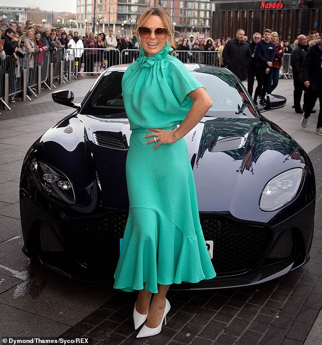 Love life: the presenter looked happier than ever while posing in front of a luxury car