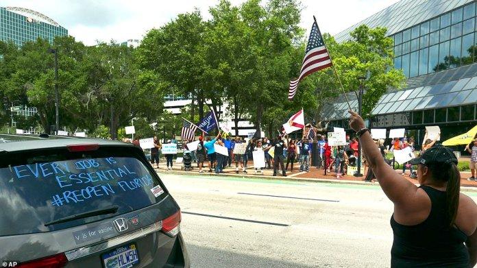 Plusieurs manifestants brandissent des drapeaux et des banderoles américaines en soutien au président Trump lors d'une manifestation à Orlando vendredi