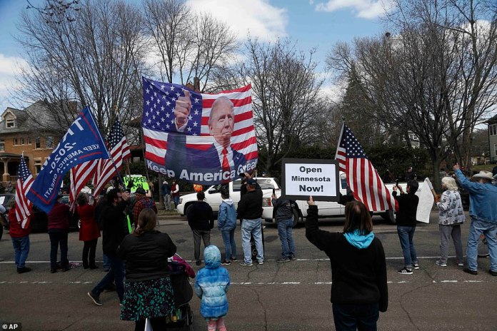 Trump banners and an American flag with the Trump likeness overlaid are waved in St. Paul on Friday.