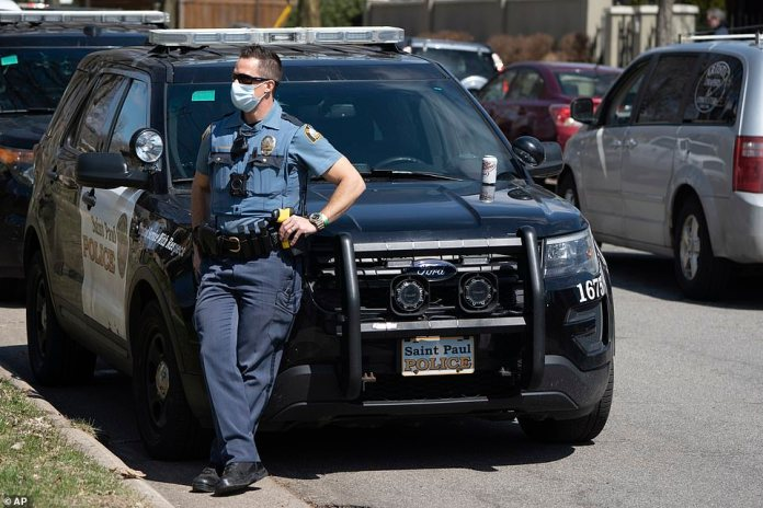 St. Paul police officer leans against his vehicle during Friday's demonstration in the state capital