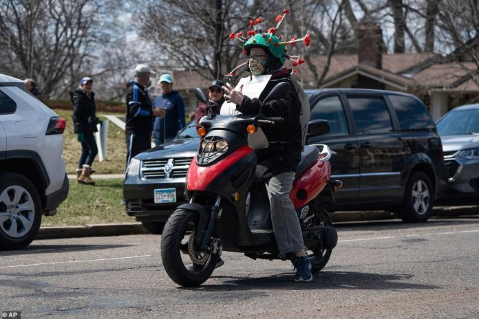 A woman above drives on a scooter while wearing a helmet designed to resemble the coronavirus on Friday