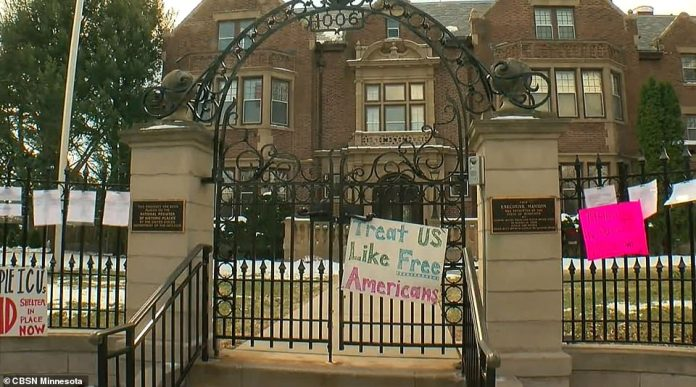 A sign attached to the fence outside the Minnesota governor's residence reads: