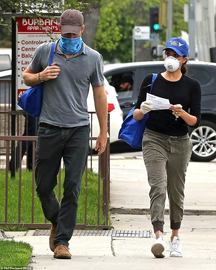 The couple walked the streets of Los Angeles with protective masks and baseball caps. Meghan also wore latex gloves while holding a sheet of paper