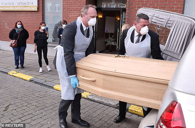 Belgium has seen a horrifying mortality rate of 45.2 per 100,000 population. Pictured: Mortuary workers load in a hearse the coffin of a person who died of coronavirus after his funeral, in Charleroi, Belgium on Saturday