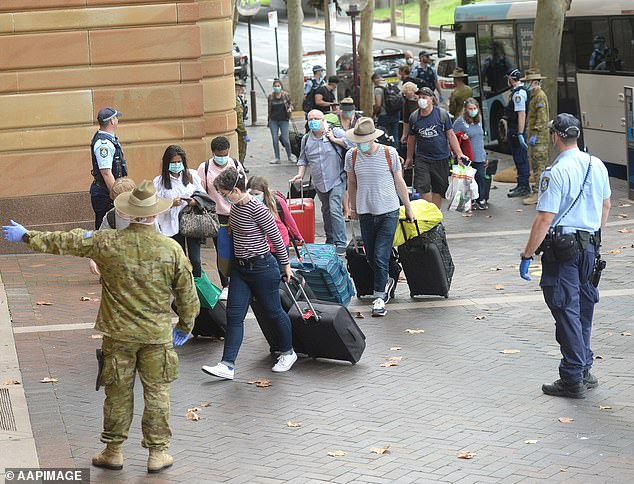 Returning overseas travellers are ushered into the InterContinental Hotel for the beginning of their 14-day imposed quarantine in Sydney