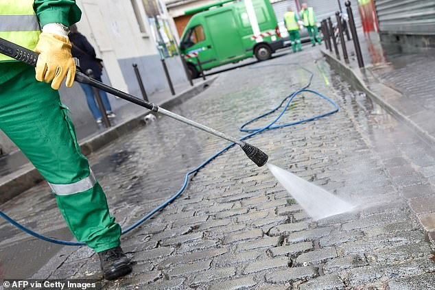 A street cleaner works along the rue de Charonne in Paris (file photo). `` Tiny traces '' of COVID-19 were discovered in the water network of the French capital, used mainly by the municipality to clean the streets