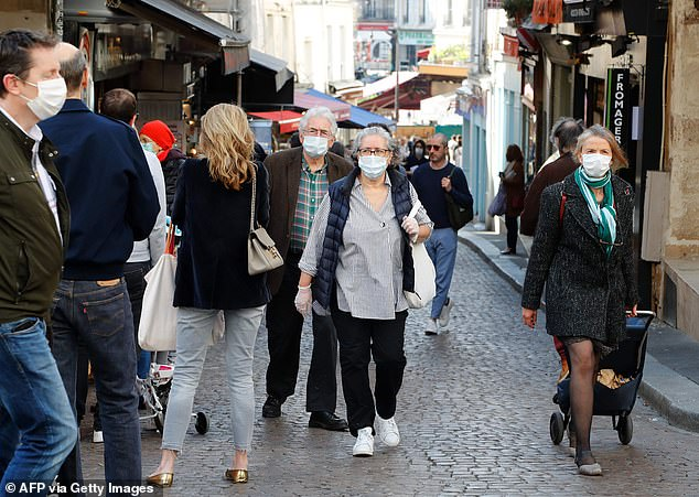 Parisians, some wearing protective masks, go shopping along rue Mouffetard in the French capital today - the 34th day of a strict lockdown in France
