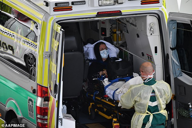 A traveller is loaded into an ambulance at Adelaide Airport on Monday. The are just170 people in hospital with coronavirus across the country, with 50 in Intensive Care Units