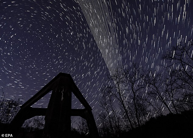 A computer-generated image from several long-exposure images shows Starlink satellites in the sky above the concrete base of a former heating plant in Hungary