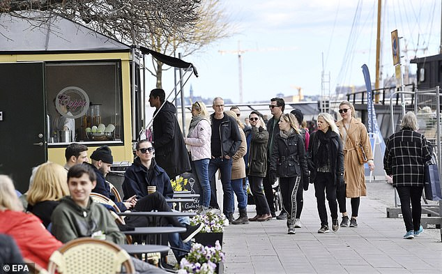 People wait to buy an ice cream - with none of the spaced-out queuing which is now familiar in much of Europe - on a street in central Stockholm yesterday