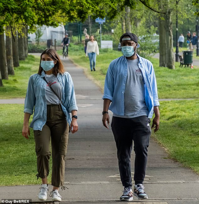 Two people are shown wearing masks on the Clapham Common in London. Face masks are only recommended for use in public transport and in stores, not mandatory