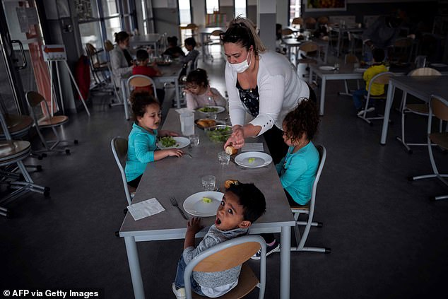 FRANCE: Children sit around a table in a school in Toulouse that has remained open to care for children of key workers such as nurses and police