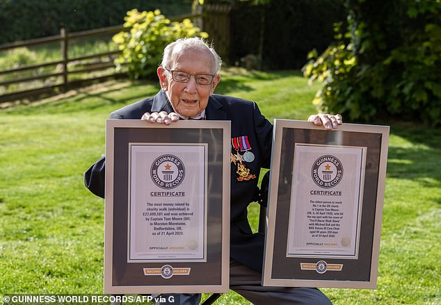 Bravo Tom! Captain Tom Moore posing with his two certificates after breaking the record for the most money raised by charity and becoming the oldest person to reach number one on the British charts
