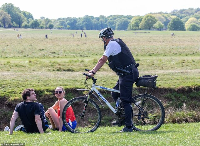 What are you doing here? A police officer stood with his bike as he spoke to a couple in Richmond Park on Sunday