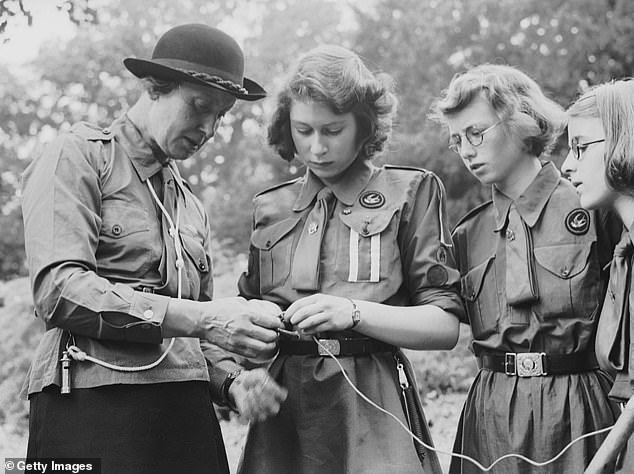Princess Elizabeth learns to tie a knot with the girl guides in Frogmore, Windsor in 1942