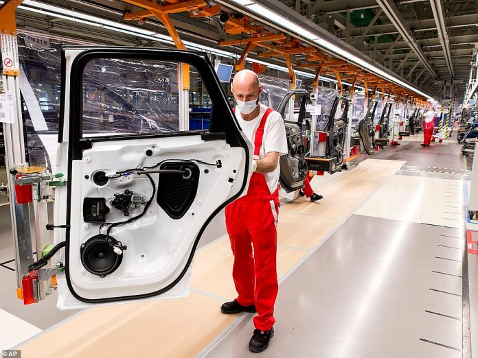 An Audi factory worker wears a mask after being allowed to return to work in Gyor, Hungary