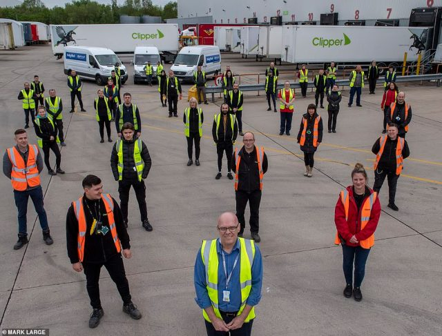 8. ... While social distancing:Staff unloading boxes of PPE at the mega-hub keep 6ft apart