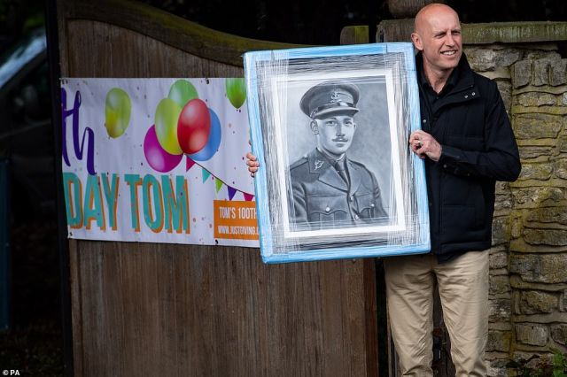 A man delivers a gift to the home of Captain Tom Moore in Bedford as he celebrates his 100th birthday