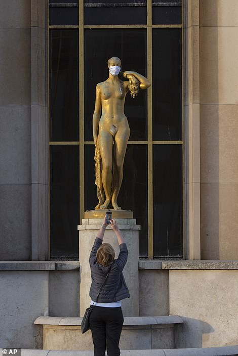 A woman takes a picture of a statue with a mask worn to encourage people to protect themselves against the spread of the coronavirus along the Trocadero square close to the Eiffel Tower