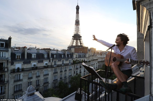 Singer Adrien Pelon aka 'Adri1' performs from his balcony for his neighbourhood in Paris, as the country is under lockdown