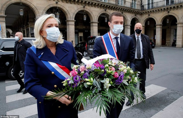 The opinion poll for Le Journal du Dimanche newspaper found only 20 per cent of French people think far-right leader Marine Le Pen (pictured laying a wreath at the Jeanne d'arc statue on Saturday) would handle the crisis better than Macron
