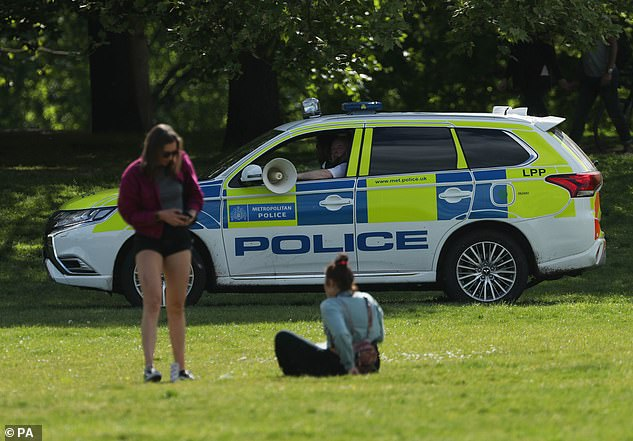 Pictured: police in a patrol car talk to bathers in Greenwich Park, London on May 2