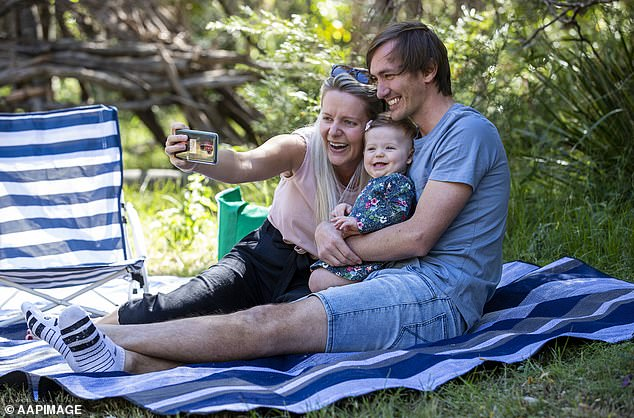 A young family enjoy a picnic at Daisy Hill Forest Park in Brisbane on Saturday as coronavirus restrictions are slowly eased across Australia