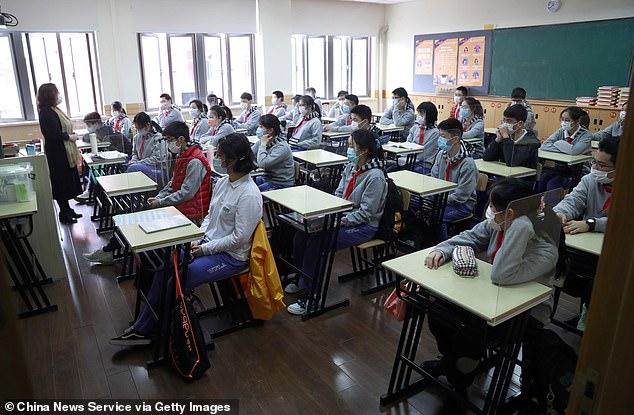 Sur la photo, des élèves portant des masques faciaux ont une classe dans un collège de Shanghai le 27 avril