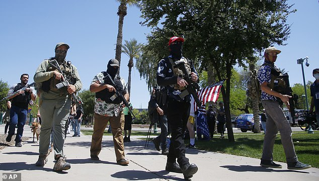 Protesters carry automatic assault rifles as they march towards Arizona's state Capitol in late April to demand the state reopen amid COVID lockdowns