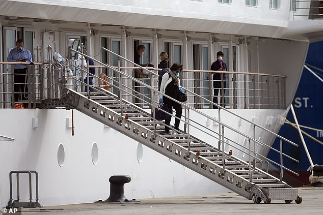 A passenger disembarks from the Australian cruise ship Greg Mortimer with others on their way to Montevideo International Airport, Uruguay, pictured last month. The ship has been anchored off the coast of Uruguay since March 27 and more than half of its passengers and crew members have been infected with a coronavirus.