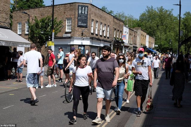 Visitors walk through a busy Broadway Market in London despite Mr Johnson urging Britons to stay at home this weekend