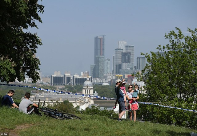 Visitors enjoying views of the skyscrapers in the City of London from a closed off viewing area in Greenwich Park, London