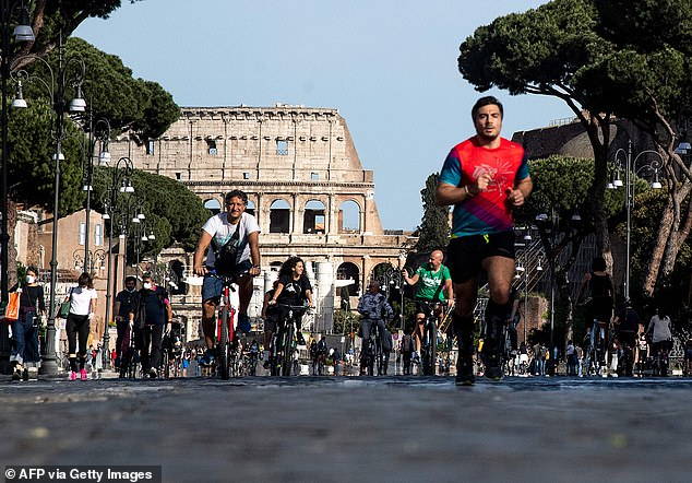 Resident cycle and jogging along Via dei Fori Imperiali in central Rome this week as the number of coronavirus cases continues to drop
