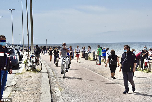 People wear masks as they walk by the sea in Livorno, Italy, as government begins to loosen lockdown measures