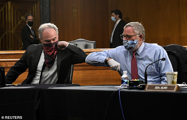 Senators Tim Kaine (D-VA) and Richard Burr (R-NC) greet each other with an elbow before the Senate hearing